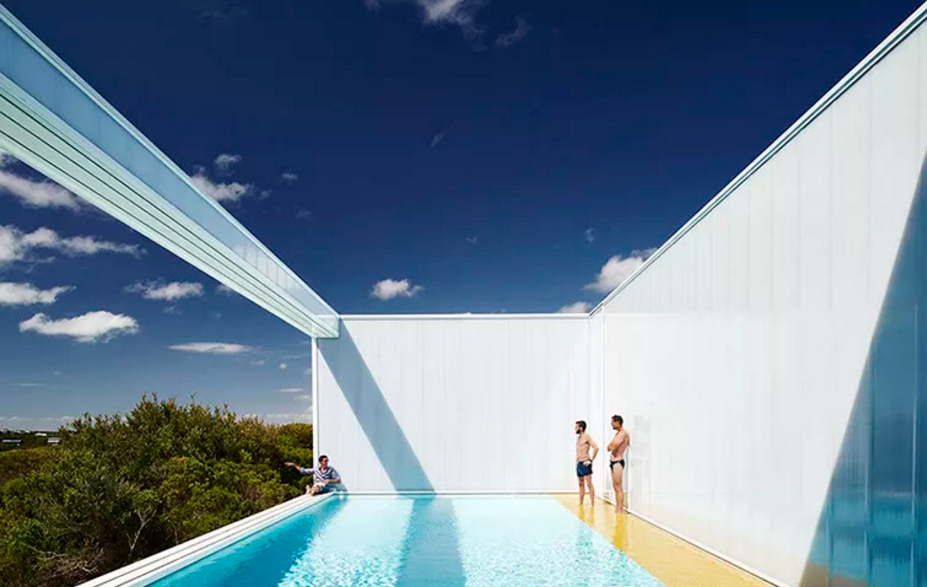 Una casa traslúcida frente al océano que se organiza en torno a la piscina acristalada