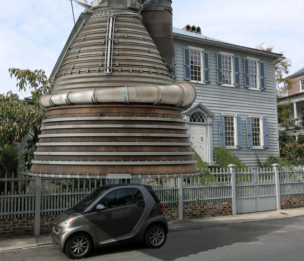 Motor de cohete M-1 (4,2 m de diámetro) sobre un Smart (2,6 m de largo) y junto a una casa típica estadounidense