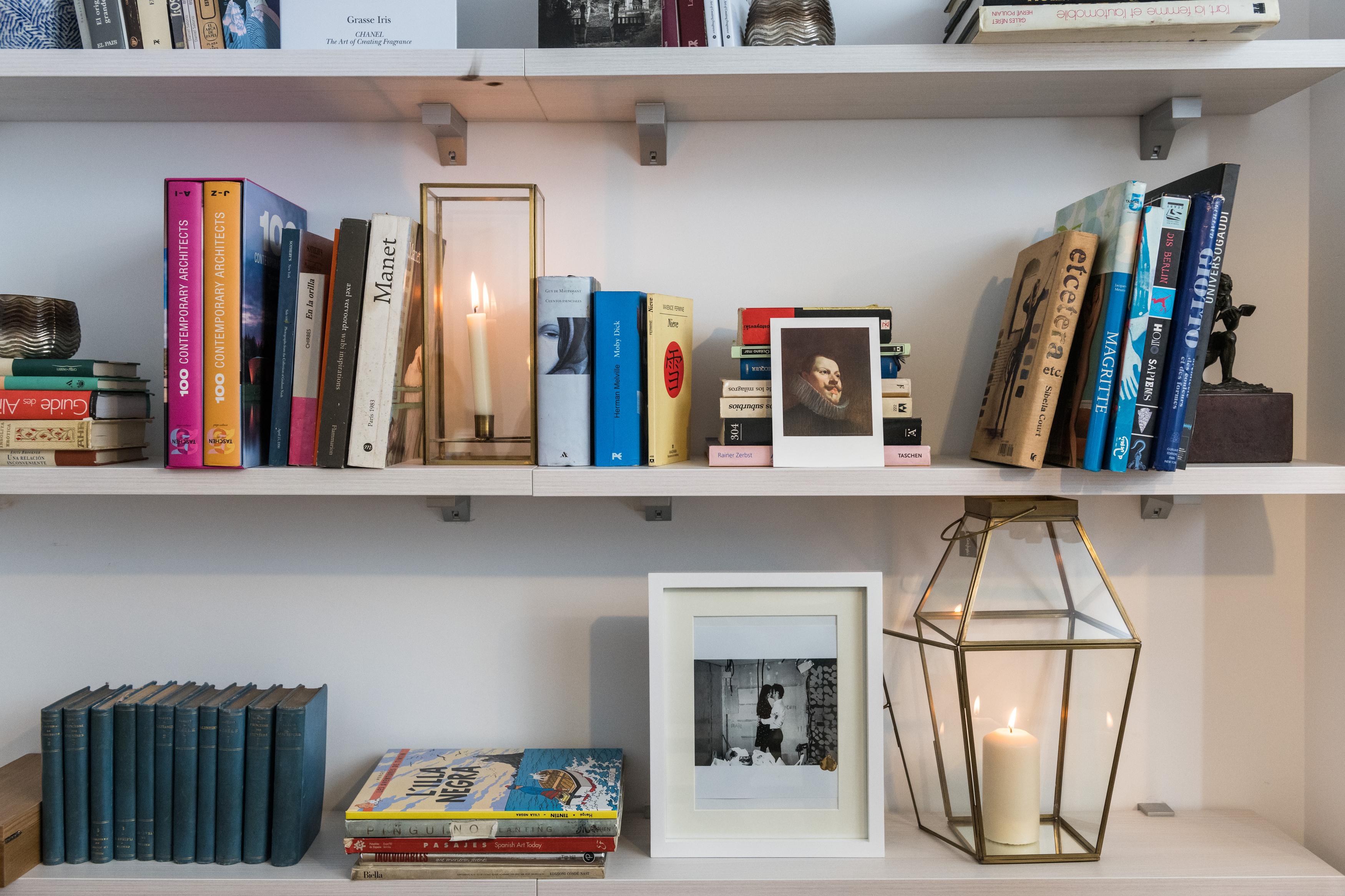 Baldas blancas blancas con libros y detalles decorativos como marcos de fotos y jarrones