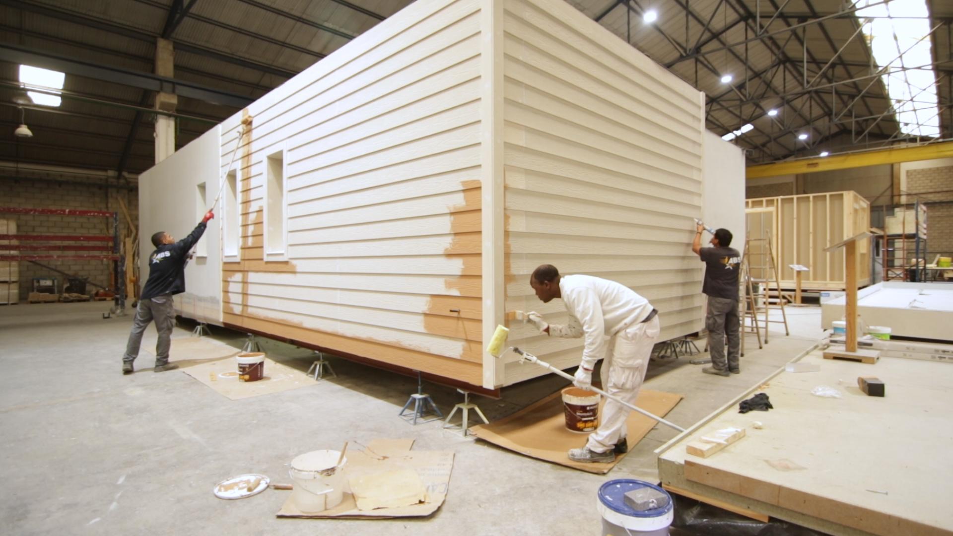 Trabajadores pintando los muros de una casa