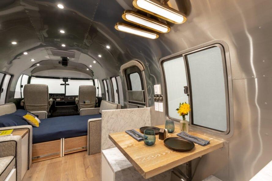 La sala de estar principal cuenta con una gran cantidad de asientos y comedor / Timeless Travel Trailers