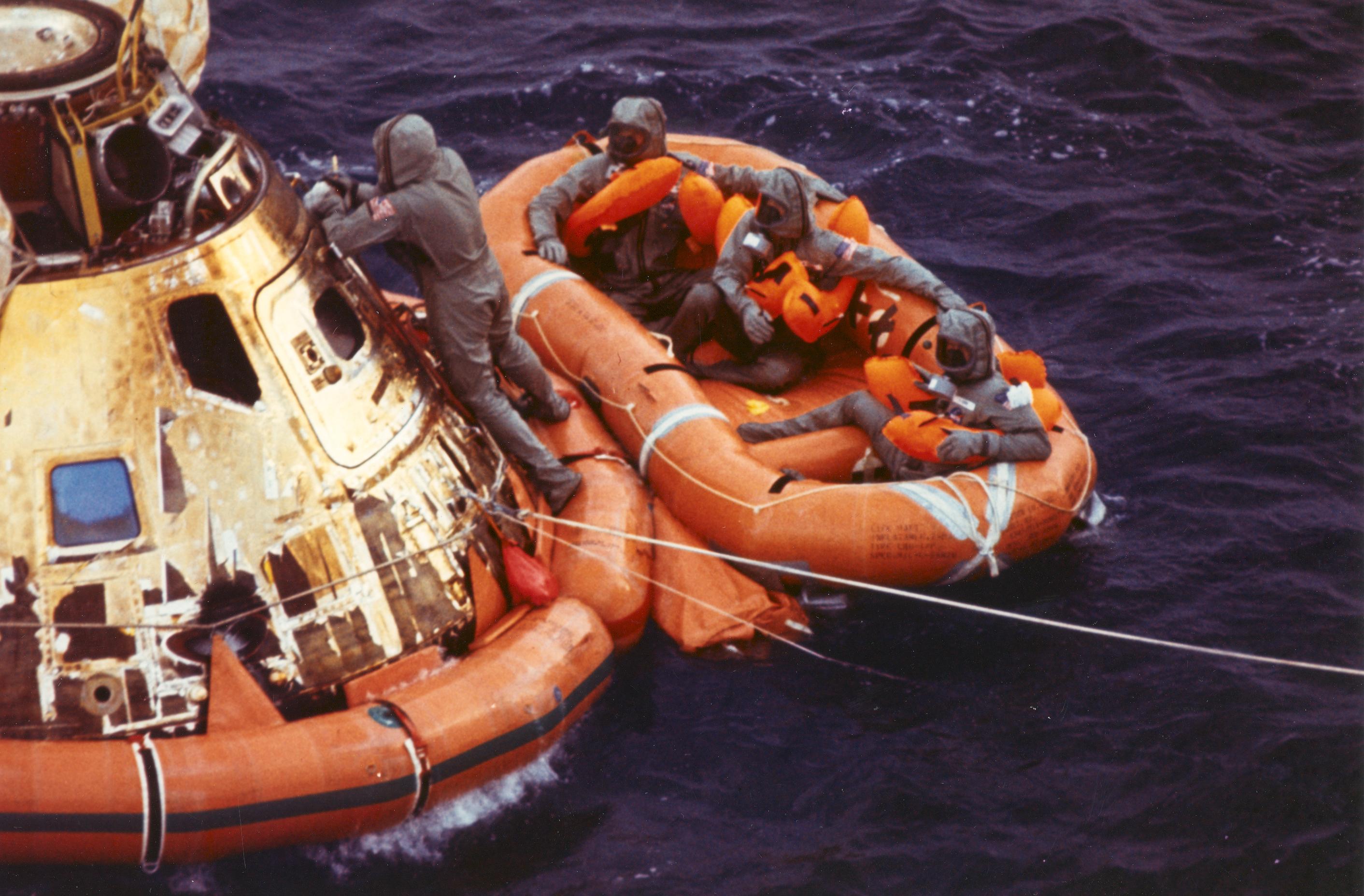 El teniente Clancy Hatleberg cierra la escotilla del Apolo 11 mientrasArmstrong, Collins y Aldrin esperan al helicóptero