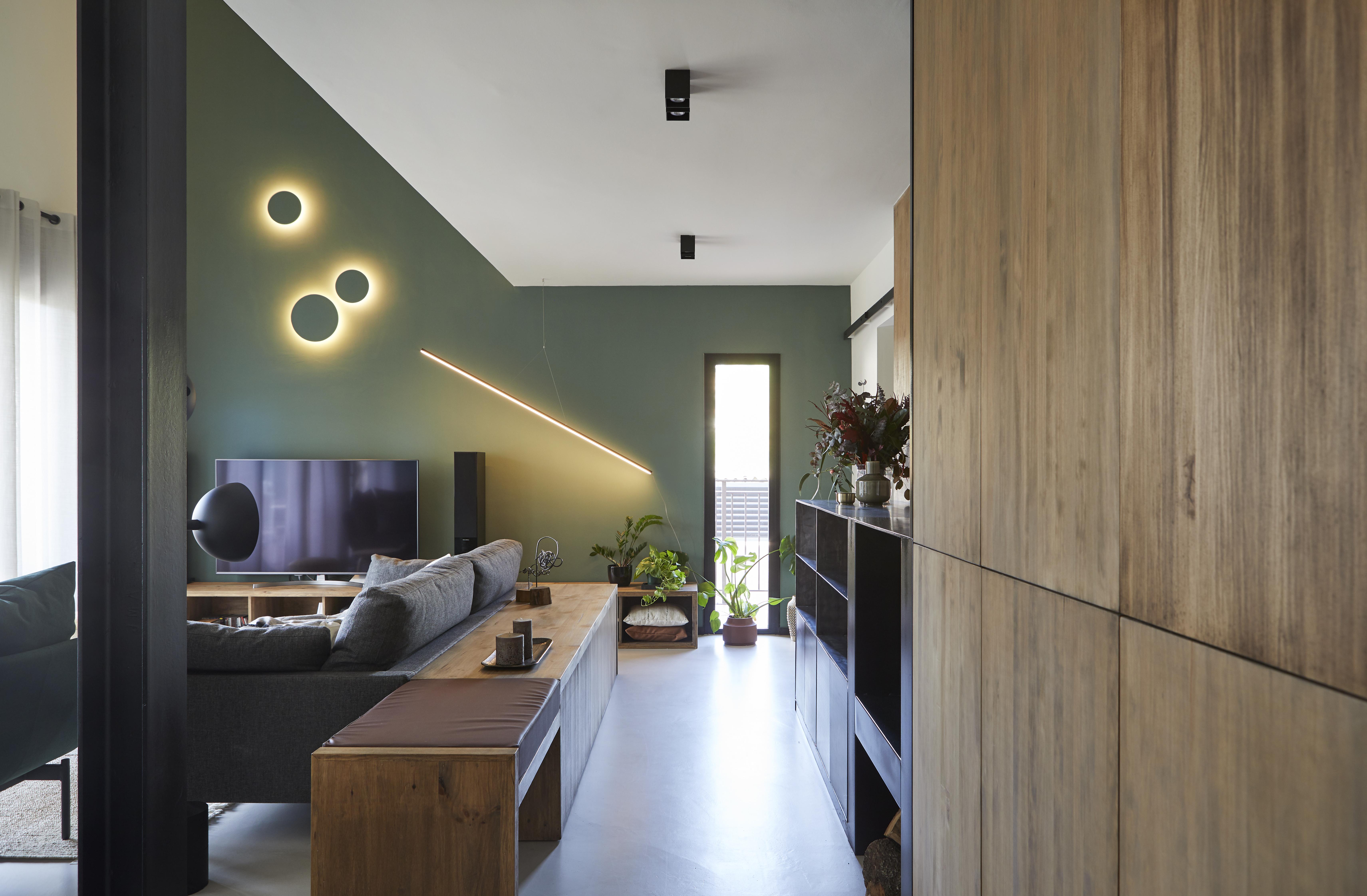 La pared verde destaca con la madera y el negro