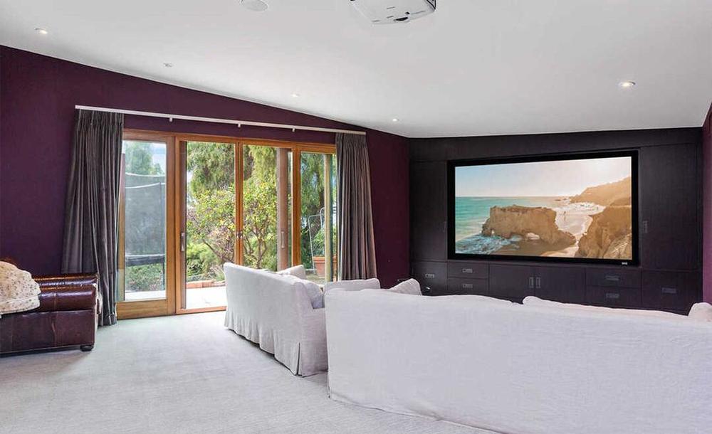 Una enorme pantalla con grandes sofás