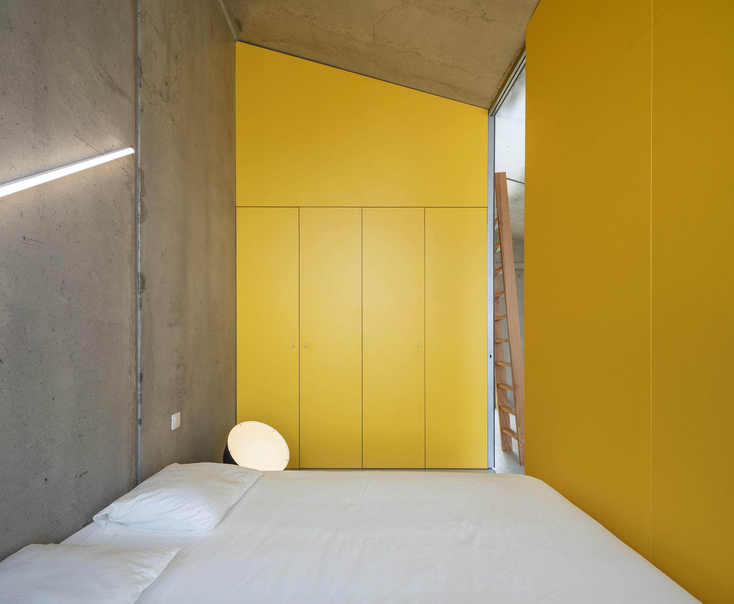 El hormigón contrasta con las paredes amarillas y los textiles blancos