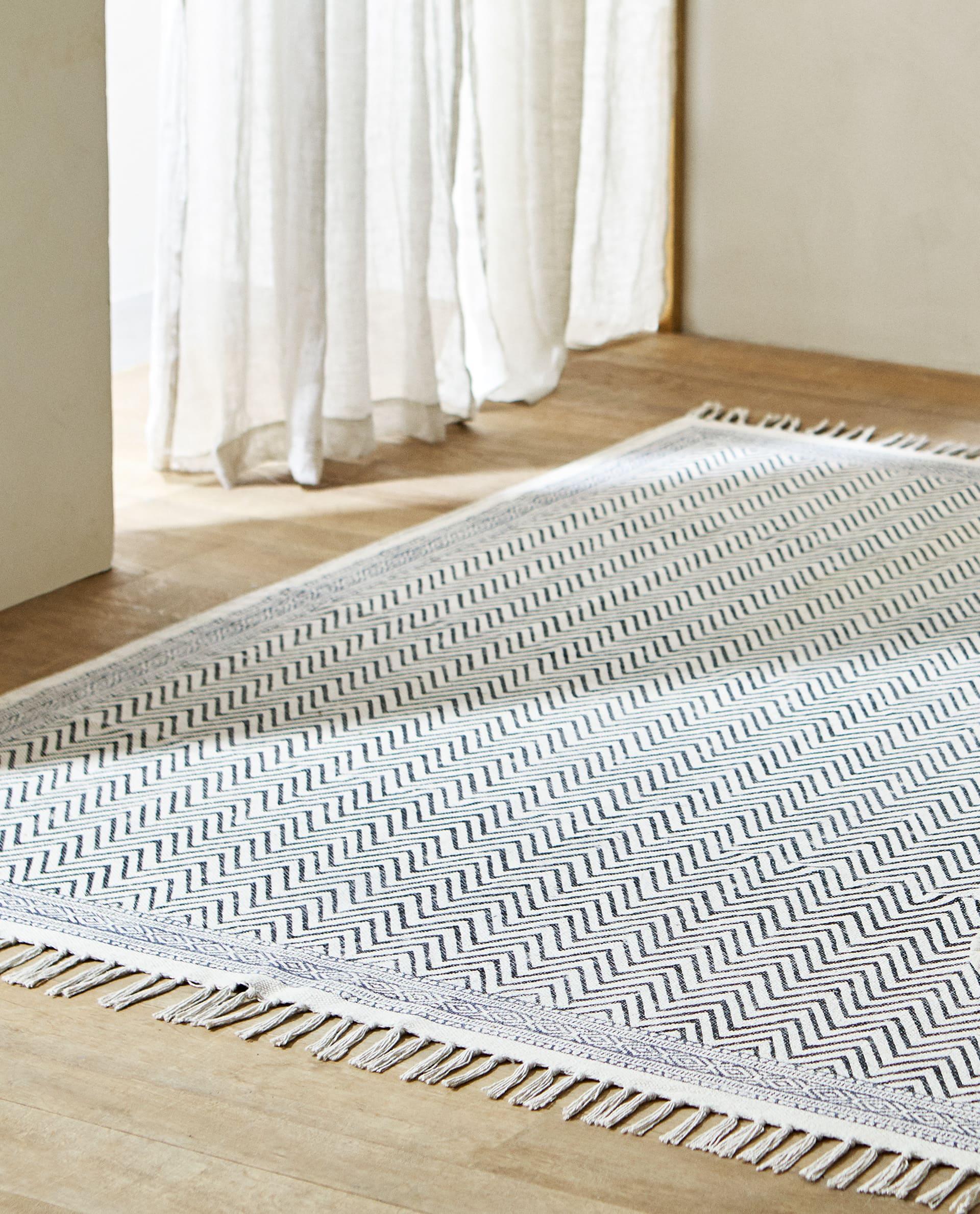 Alfombra de algodón con estampado en zigzag en tonos grises de Zara Home (29,99 euros) / Zara Home