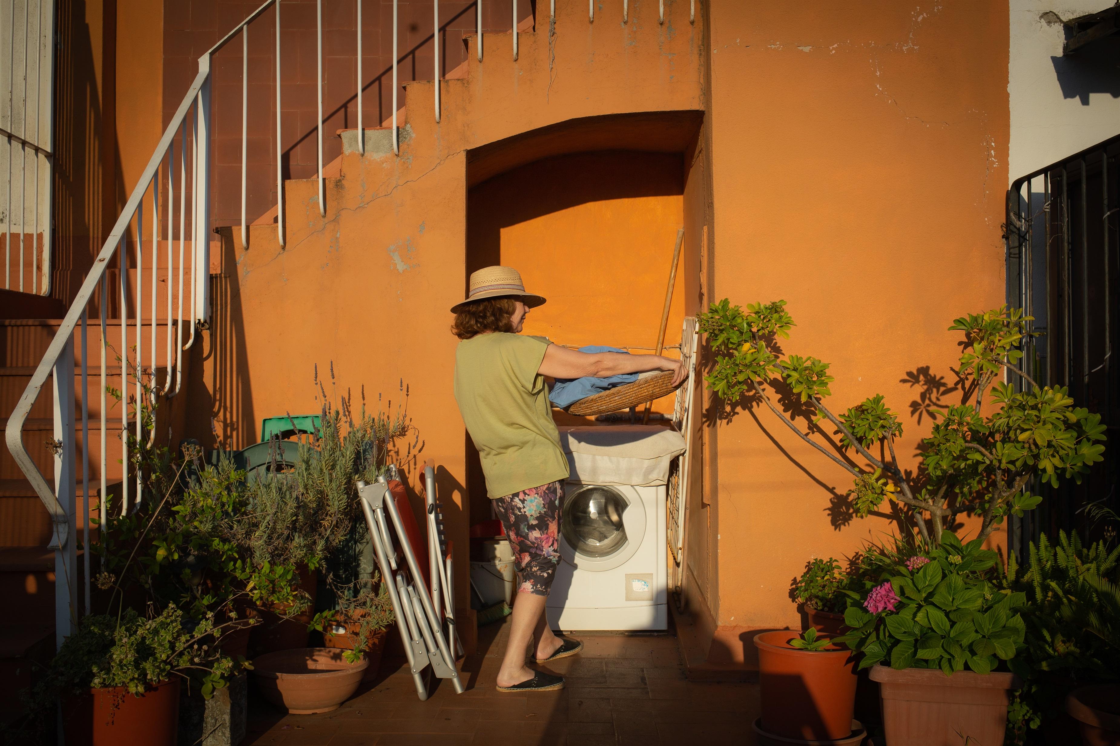 Una mujer ante una lavadora en una terraza - DAVID ZORRAKINO