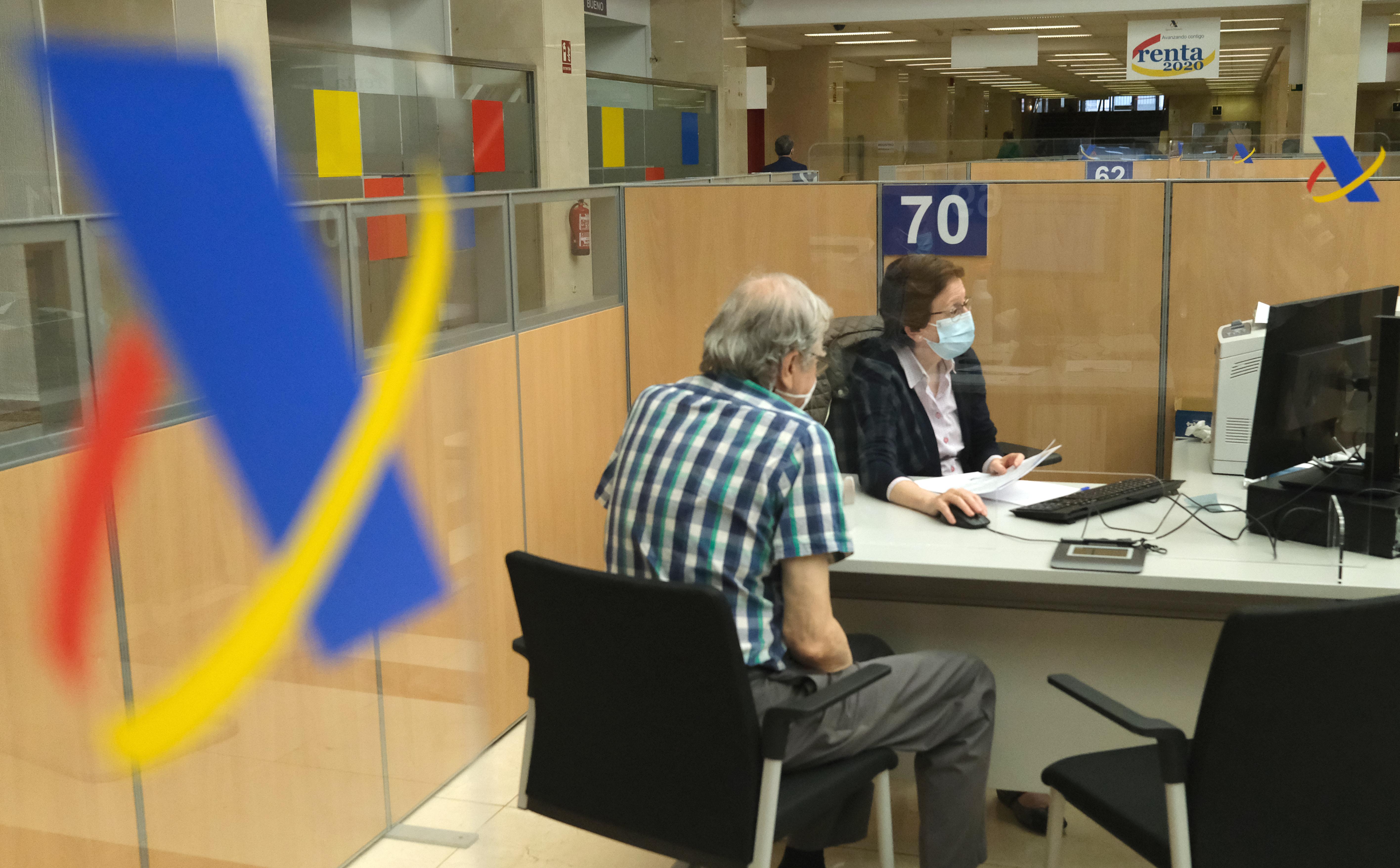 Una empleada atiende a una persona de manera presencial desde una oficina de la Agencia Tributaria
