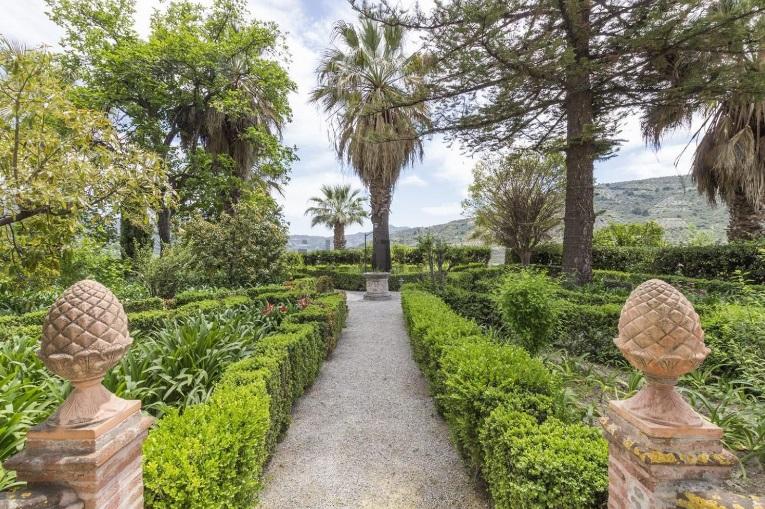 Con palmeras centenarias, plantas exóticas y cipreses antiguos