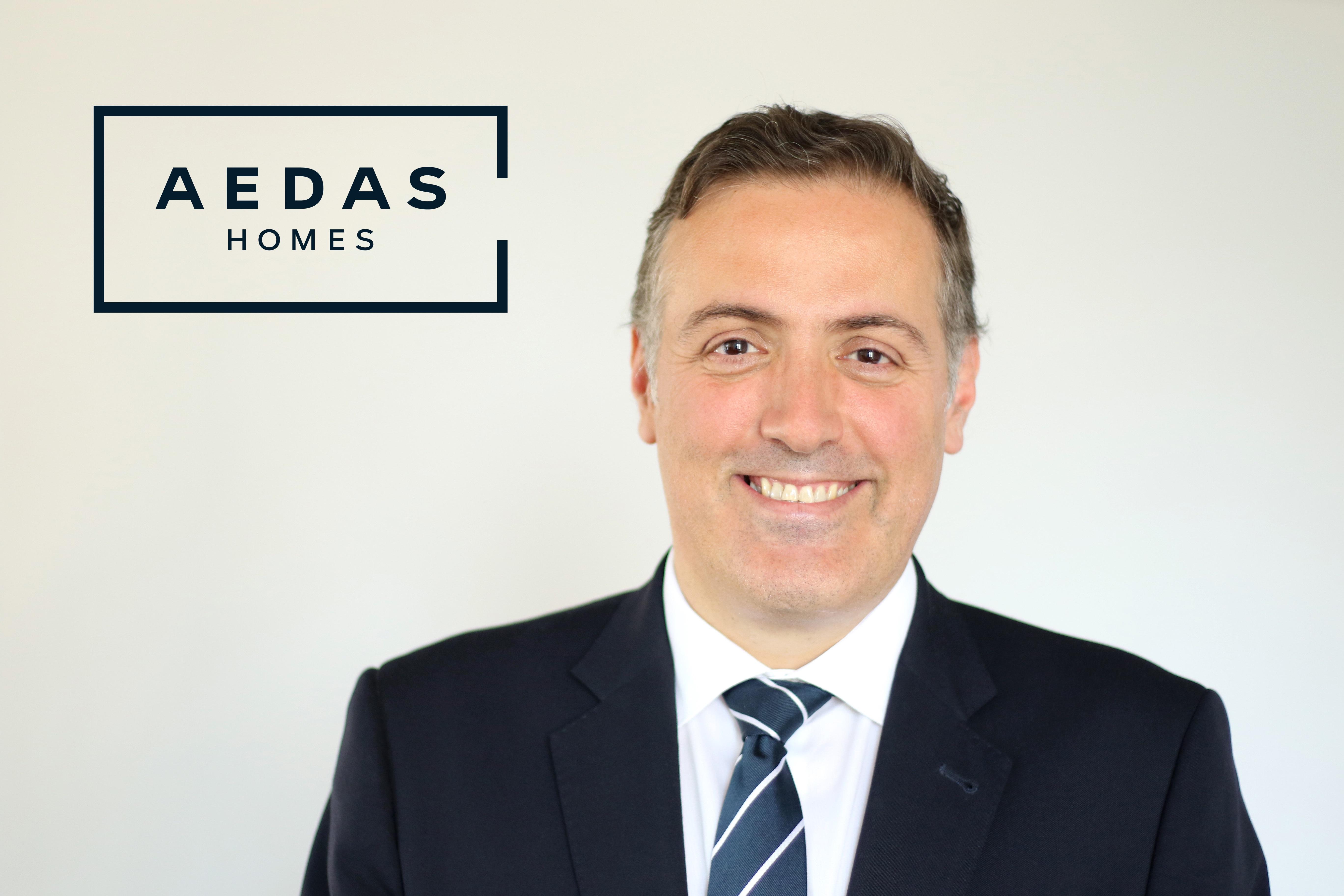 El Consejero Delegado de AEDAS Homes, David Martínez, posa delante del logo de la empresa / AEDAS HOMES