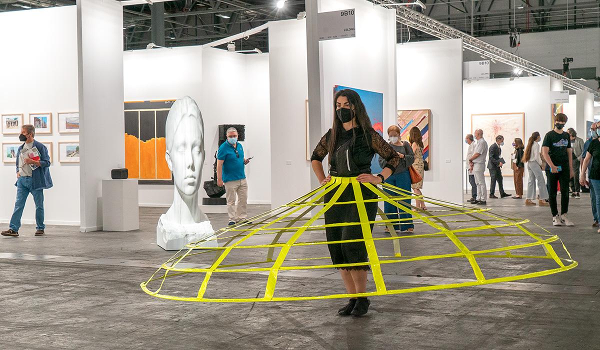 Artista realizando una performance con una escultura de Jaume Plensa al fondo
