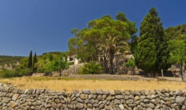 Rodeada de árboles y un muro de piedra