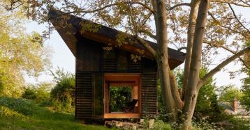 Una minicasa de madera hecha para vivir en medio del campo o del jardín