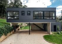 Imagen 0 - Una casa prefabricada de dos volúmenes e integrada en la naturaleza de Brasil