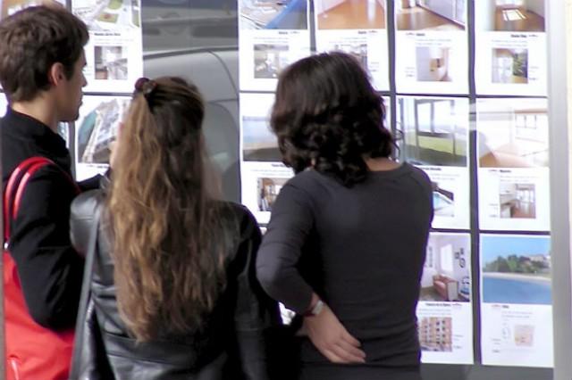 jóvenes mirando una inmobiliaria